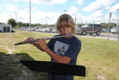 Outside the band room, freshman Jake Bursk practices his flute.