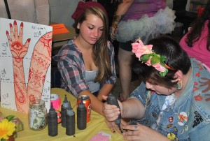 Junior Peyton Oller applies a henna tattoo to junior Maddie Leary.
