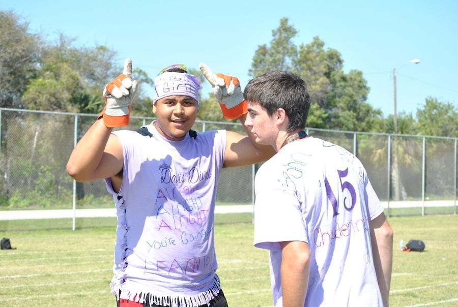 Celebrating a victory, juniors Chad Goodman and Justin Cruz show of their tug-o-war-aiding garden gloves.