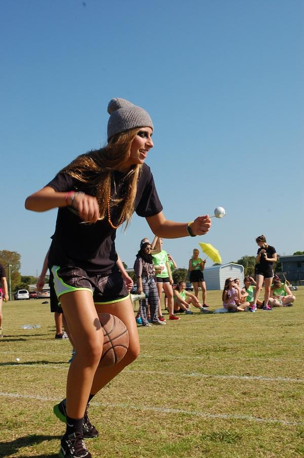 Taking great care, junior Angela Ahern balances an egg on a spoon and a basketball between her legs in a field game.