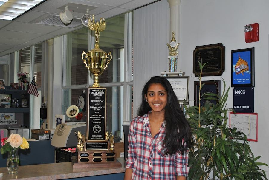 In the front office, sophomore Srimayi Tenali displays her science fair trophy.