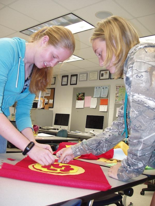 Sophomores Brooke Townsend and Jessica Knowles work on their home room flag before school on Sept. 19.