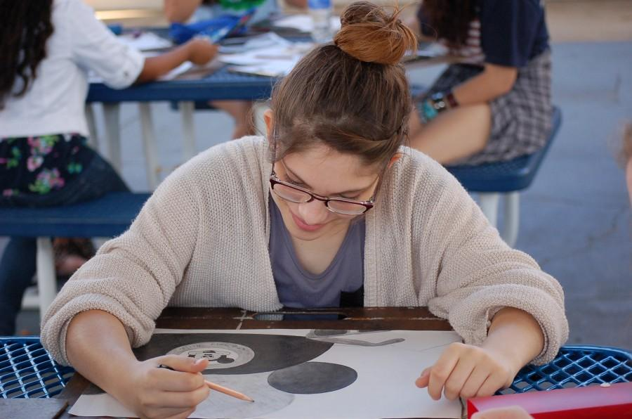 """Sketching off of a photograph, tenth grader, Kayelee Embry puts the finishing touches on her still life classroom project. """"I'm so happy to be able to include my love for Disney within an actual class at school,"""" said Embry."""
