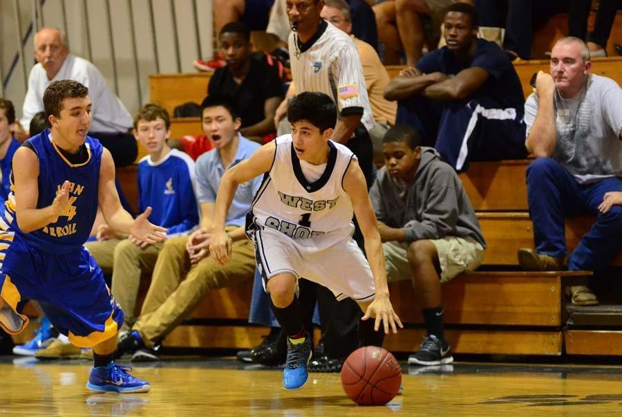 Sophomore Juan Rodriguez dribbles down court against  John Carroll.