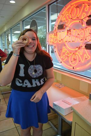 Sophia Pietrazak embraces her good grades with a box full of free donuts at the local Krispy Kreme.