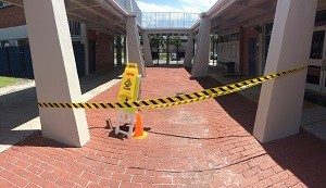 Caution tape and cones mark the spot where a pothole opened in front of the school cafeteria