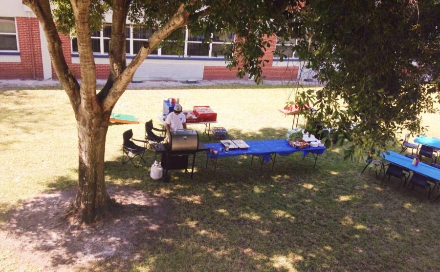 Preparing before the teachers arrive for lunch, Robert Farrell starts to put some meat on the grill.