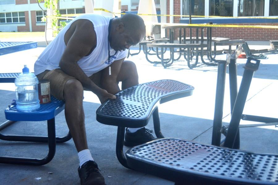 Custodian Derrick Hamilton assembles one of the tables donated by Five Guys,