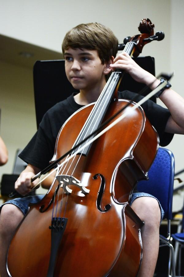 Focusing+on+playing+a+scale%2C+eighth+grader+Timothy+James+Z.+watches+his+teacher+conduct+the+class.+%22I%27ve+been+playing+the+cello+for+four+years.+I+started+because+I+had+an+interest+in+music.%22+Taking+on+the+role+of+first+chair+cello++Timothy+James+helps+lead+his+section.+