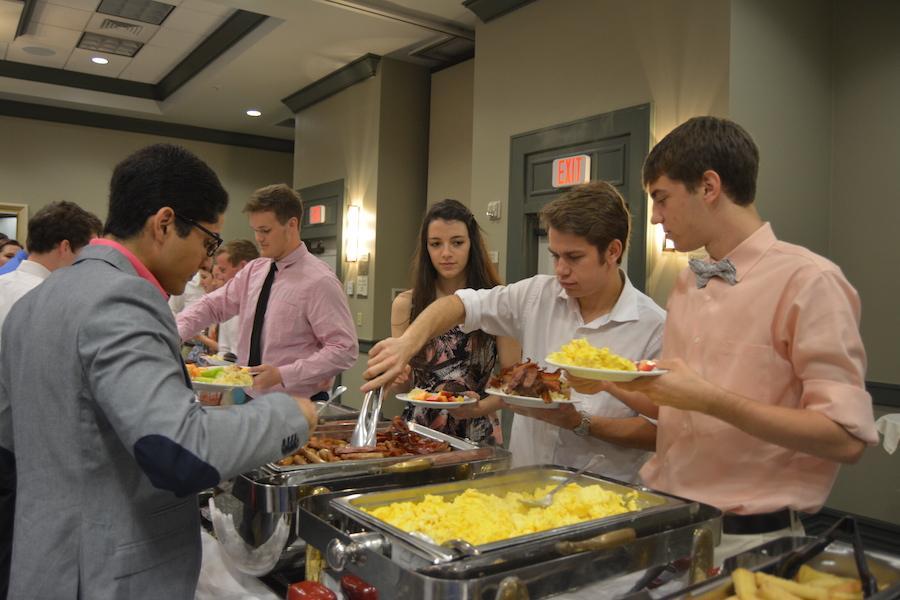 Kassie West, Stryker Sinclair, and Ben Mechachonis get food during the 2014 Senior Breakfast.