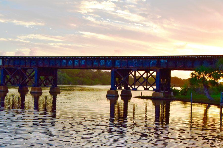 """As the sun sets over Crane Creek Promenade in Melbourne, the bridge reads """"More Love,"""" a statement that serves as a call to action to help the Indian River Lagoon,"""
