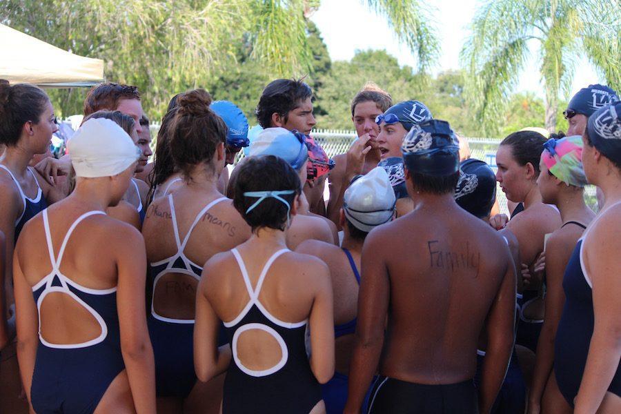 Swim Team listens to a pre- meet speech before swimming.