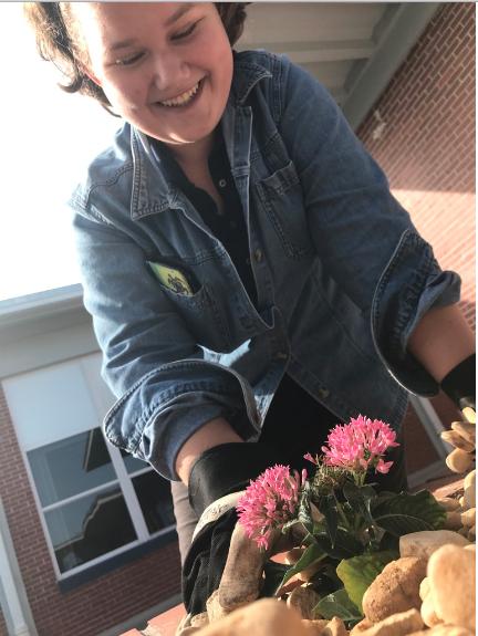 Freshman Julia Travis gardens around Whitworth the Wildcat with a radiant smile.