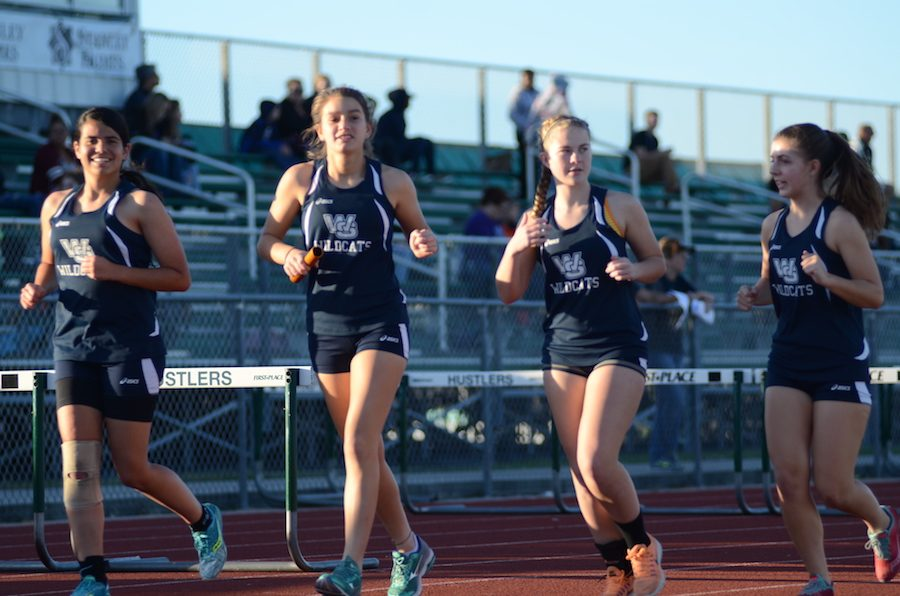 Members of the girls' track team warmup ahead of a race.