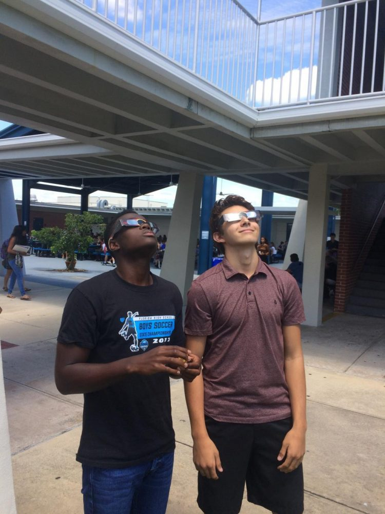 Senior Liam Wiles and junior Robbie Dujovne use their solar eclipse glasses to look at the sun.