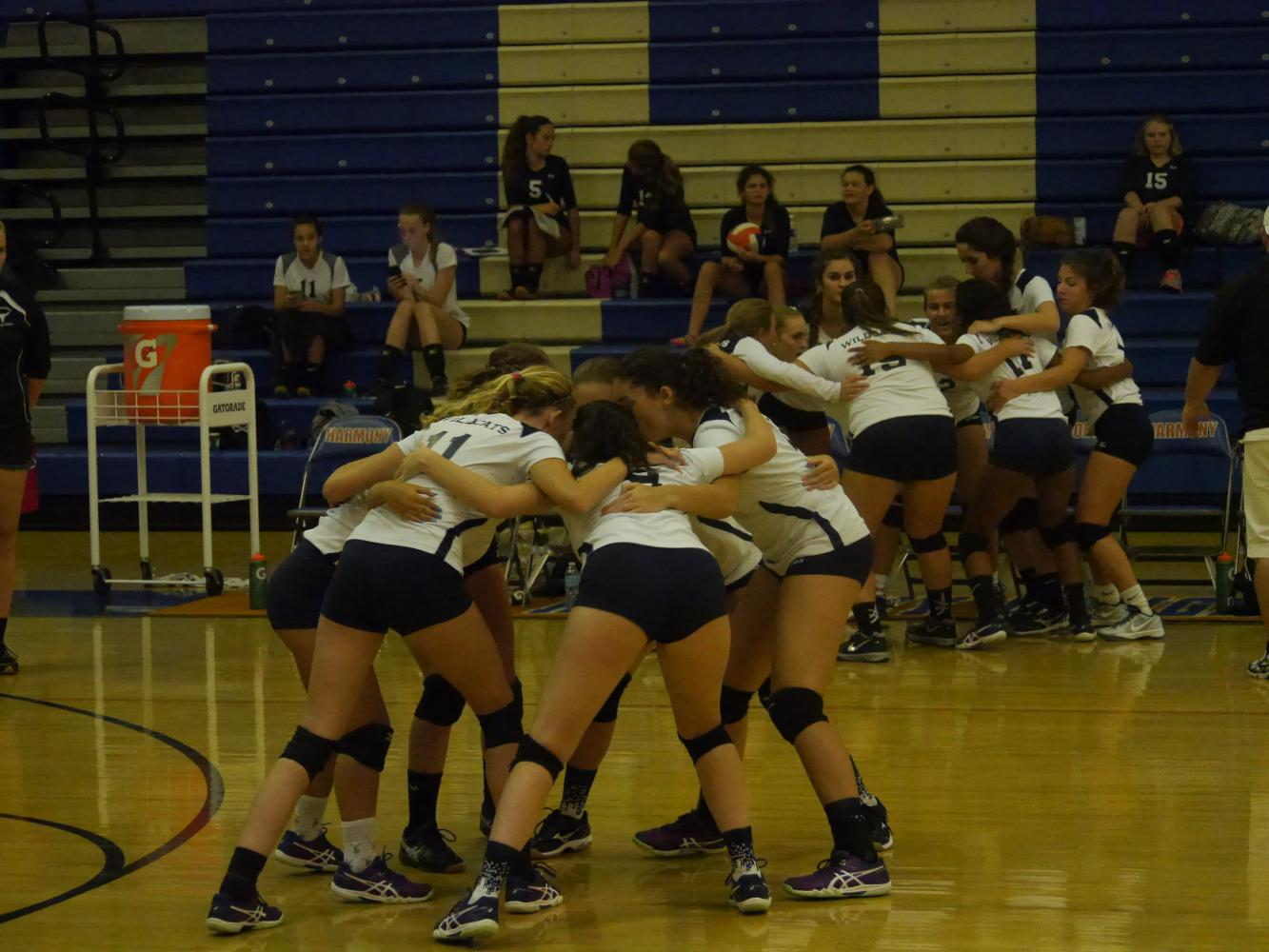 The varsity volleyball team gathers together before an important game.