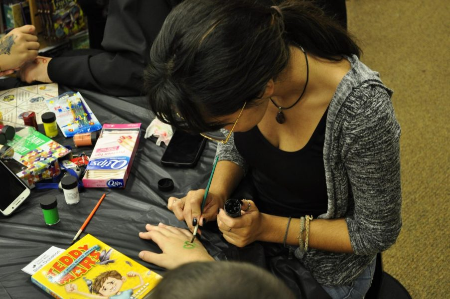 Emily Ortiz paints a green snake on a little boy's hand Wednesday night.