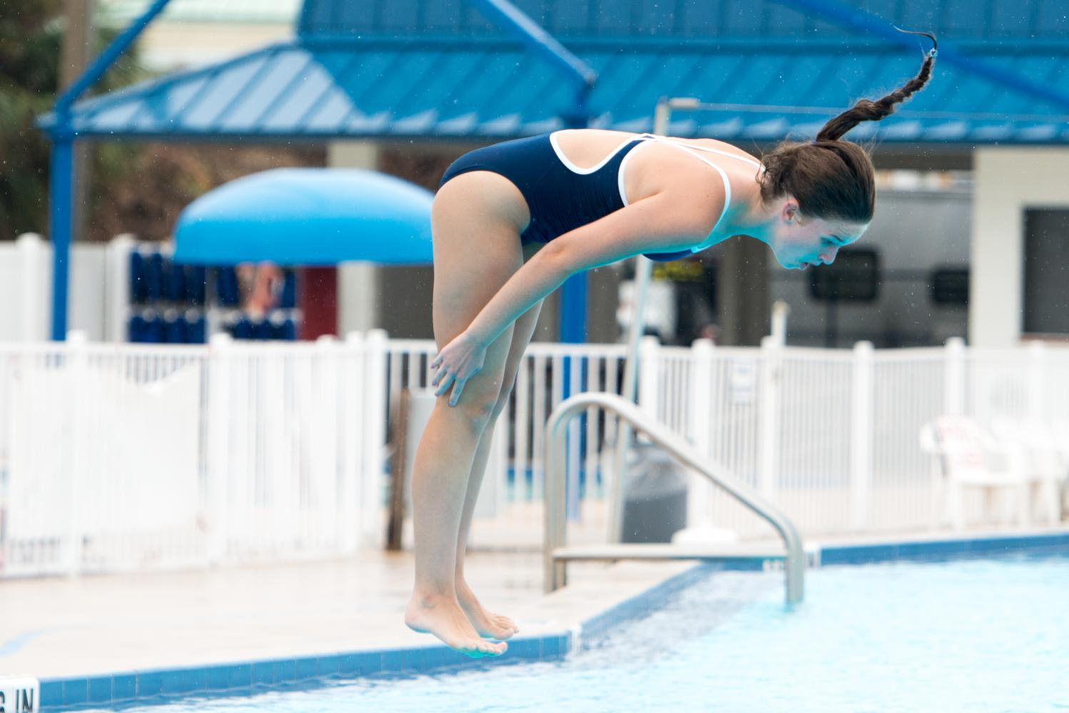 Junior Lauren Seifert performs a tucked dive during the Cape Coast Conference meet.