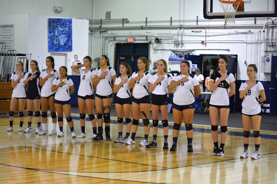 The varsity volleyball team taking the pledge before their game.