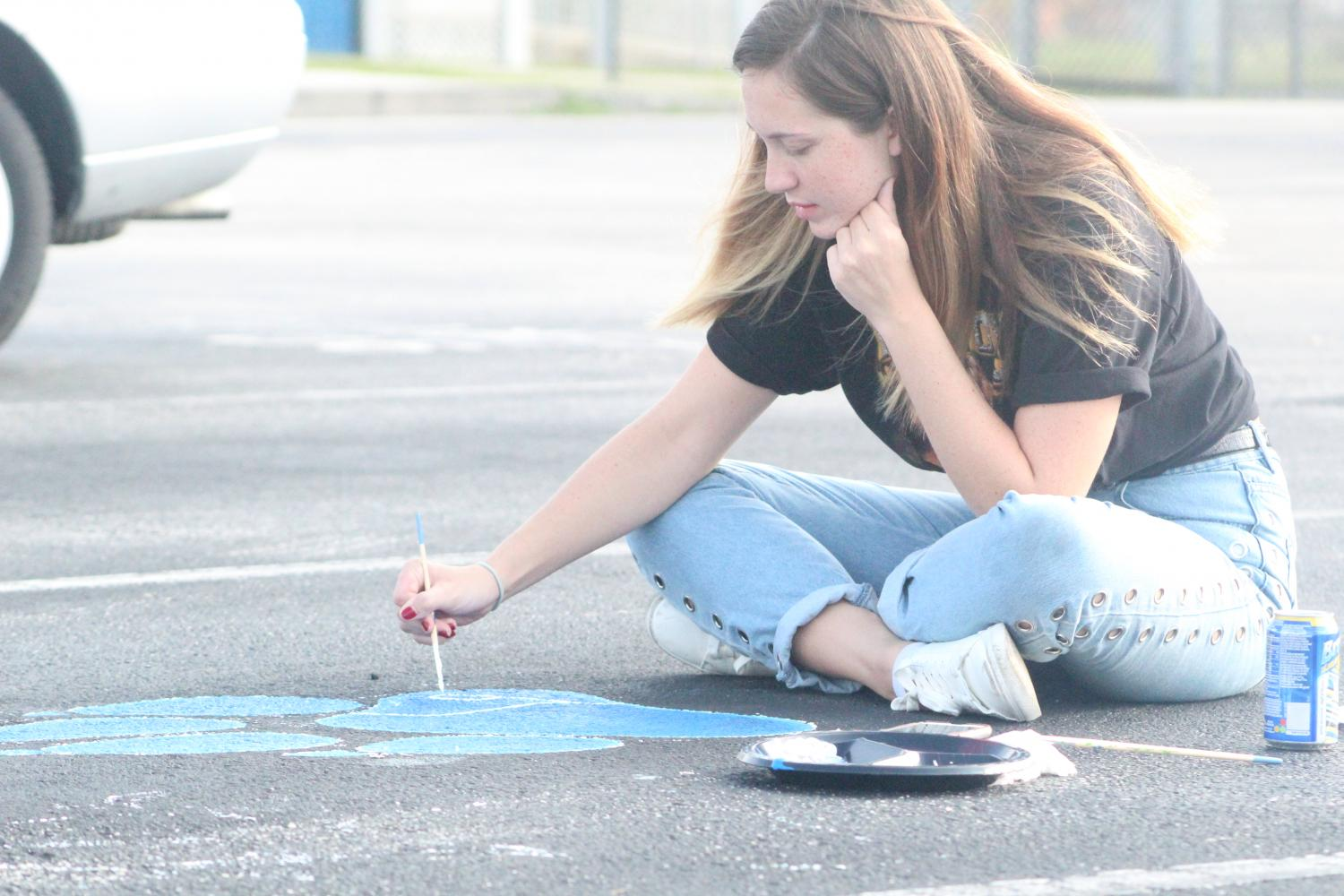 Senior Joanae Lawrence paints her parking spot on Saturday, Sept. 30.