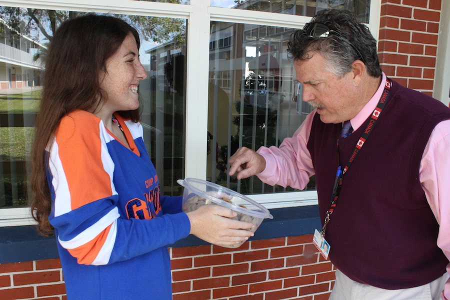 Senior Lily McKnight shares some of her homemade cookies with Principal Rick Fleming on Thursday.
