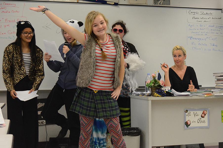 Freshman Cassidy Kuhar walk the runway in a French fashion show as teacher Jennifer Walker looks on.