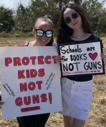 "Attending the March for Our Lives protest, sophomores Isabel Burden and Sarah Paylor carry signs in protest to call attention to the government for a reform on guns. "" It's time for action and for the young people to finally be heard,"" Burden said."