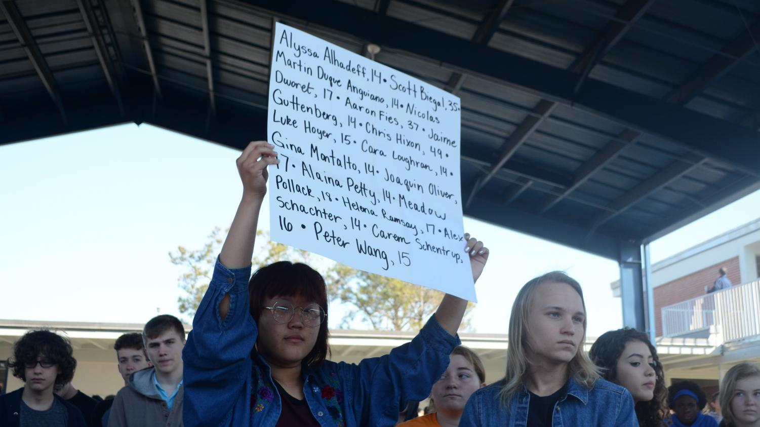 Freshman Hanna Sheinman held up a poster containing the names of those who died for the duration of  the 17-minute vigil.
