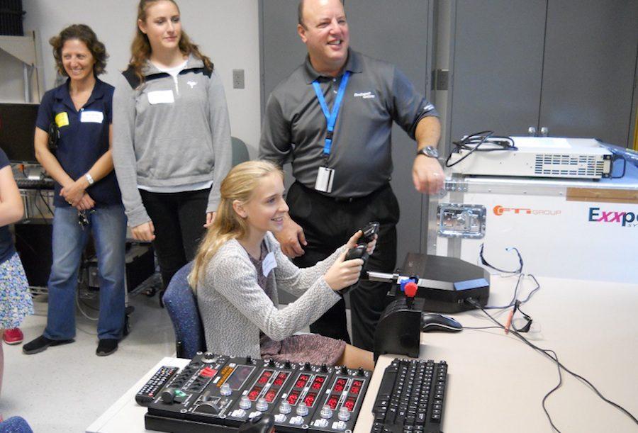 Freshman+Kelly+Logan+operates+a+flight+simulator.