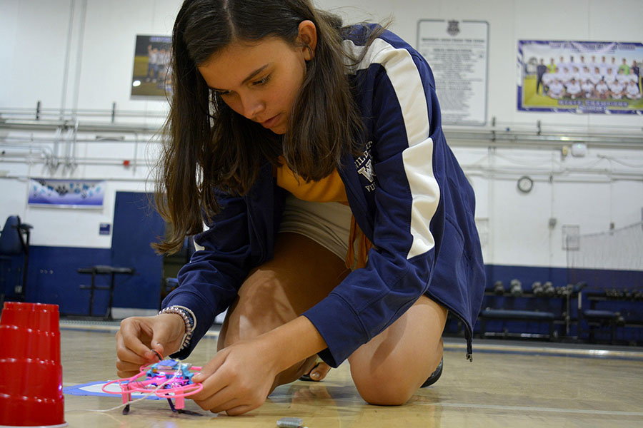 Eighth-grader Abby H. changes the battery on her drone.