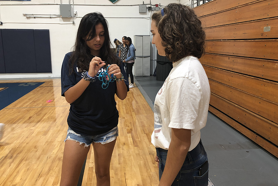 Varsity member of the Whirly Girls, Grace Mendese, helps JV member Beatrice P. with the drones.