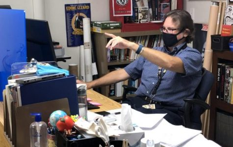 History teacher Kirk Murphy instructs humanities from behind his desk barrier.