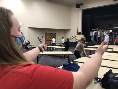 "Haley Tucker (11) directs drama students to move tables in the auditorium in order to create a barrier between high school and middle school students. ""It helps them work more efficiently,"" said Tucker."