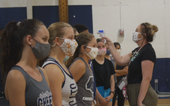 Coach Kaitlyn Hoskins performs a temperature check on the cheer squad before practice.