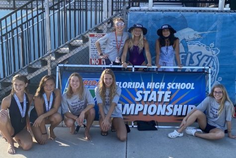 Eliza H. (8), Lillian Altman (10), Kalia Clary (11), Ava Auter (10) and Nicole R. (8) pose in front of the state championship banner with Allison Clark (11), Layla Auter (12), and Katelyn Owl (12) behind it. (Kyle Berry)