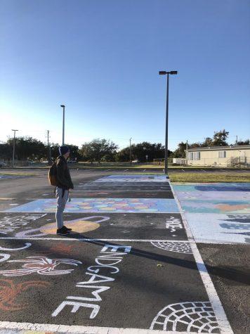 Senior Evan Ratkus walks around the auditorium parking lot before school starts.