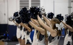The cheer team holds their pom poms up in hopes the team makes their free throws.