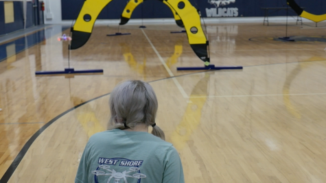 Freshman Arabella Dias monitors the trajectory of her drone in as she guides it through an obstacle course in the gym on Feb. 19.