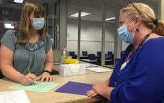 Media specialist Amy Franco signs off on English teacher Kim Bracken's checkout sheet Monday.
