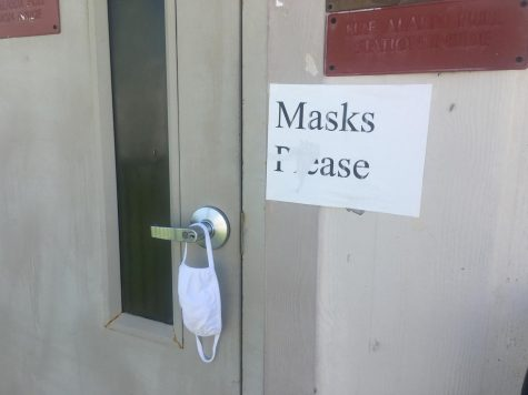 Outside of Kirk Murphys portable, a request for Masks Please is posted.